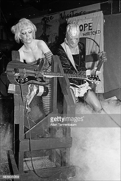 American musician Wendy O Williams of the group the Plasmatics chainsaws a guitar onstage at CBGB New York New York March 1 1979 Bassist Richie...