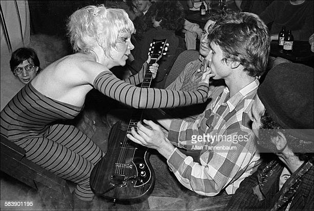 American musician Wendy O Williams of the group the Plasmatics puts her fingers in the mouth of a fan at CBGB during a concert New York New York...