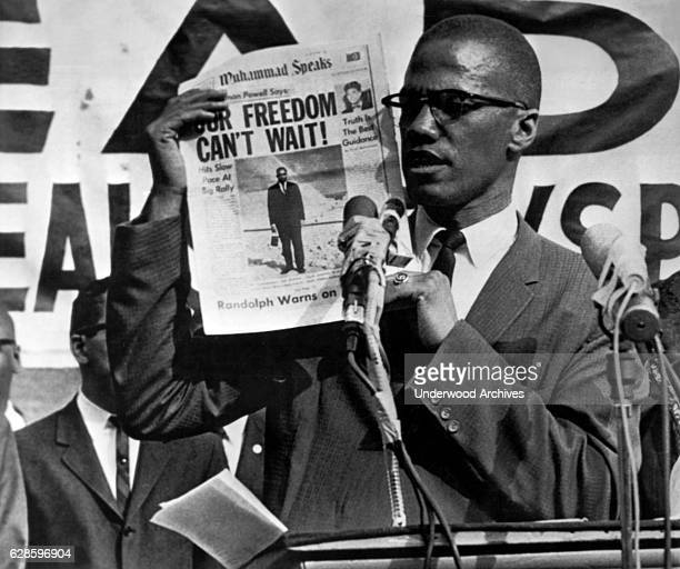 American Muslim leader and activits Malcolm X holds up an issue of the Muhammad Speaks newspaper during a rally New York New York July 27 1963