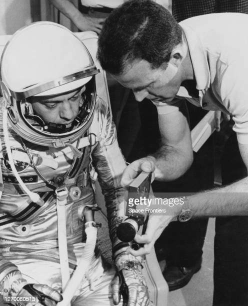 American NASA astronaut Alan Shepard receiving instructions by American NASA astronaut Gordon Cooper on how at use a 16mm handheld camera at Cape...