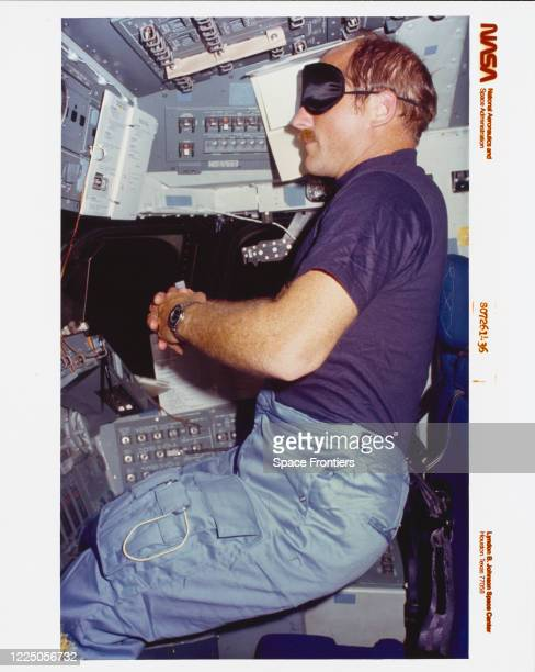 American NASA astronaut and pilot Frederick Hauck, wearing sleep mask and with arms folded in front of his chest, sits for an experiment in forward...