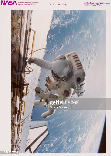 American NASA astronaut Dale Gardner tethered to the starboard side of the Space Shuttle Discovery during extravehicular activity as part of Shuttle...
