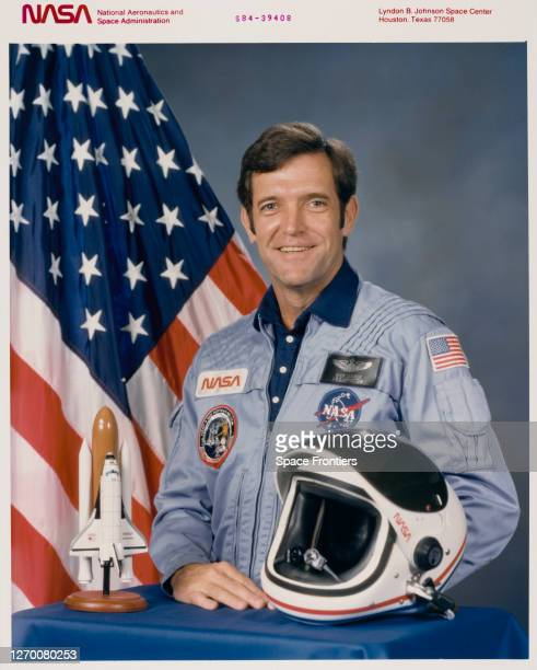 American NASA astronaut Dick Scobee wearing a blue NASA jumpsuit smiling in a studio portrait beside the American flag and a model of a space shuttle...