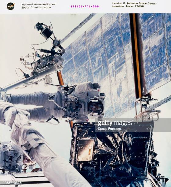 American NASA astronaut John M Grunsfeld positioned on a foot restraint on the end of the Remote Manipulator System as he looks to replace a radio...