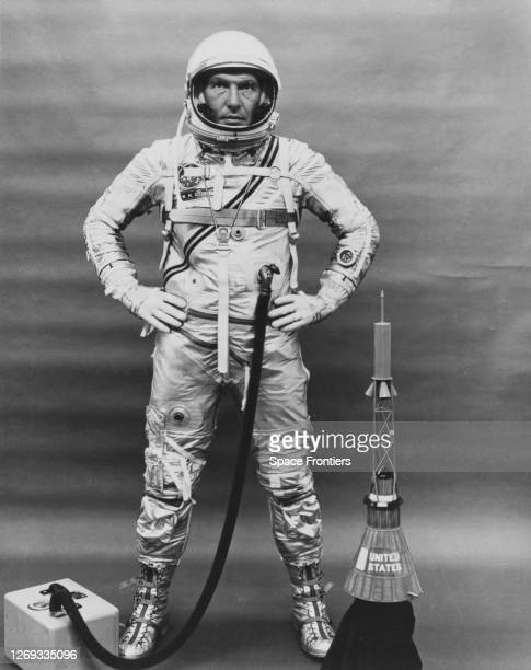 American NASA astronaut Wally Schirra backup pilot for the MA7 stands completely suitedup his hands on his hips with a portable air conditioning unit...