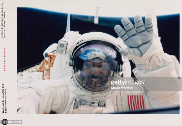 American NASA astronaut Winston E Scott waves to his crew mates inside the crew cabin from the cargo bay of the Space Shuttle Endeavour during his...