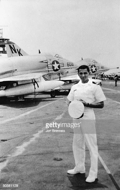 American Naval Officer Lt Everett Alvarez posing in uniform next to Navy fighter planes before he was taken prisoner by the Vietcong