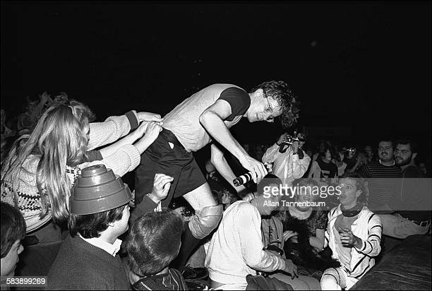 American New Wave musician Mark Mothersbaugh of the group Devo climbs among concert goers during a performance at Radio City Music Hall New York New...