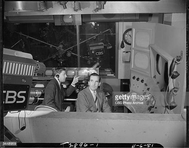 American news producer and director Don Hewitt points on the set of the CBS news program 'See It Now' while broadcast journalist Edward R. Murrow...