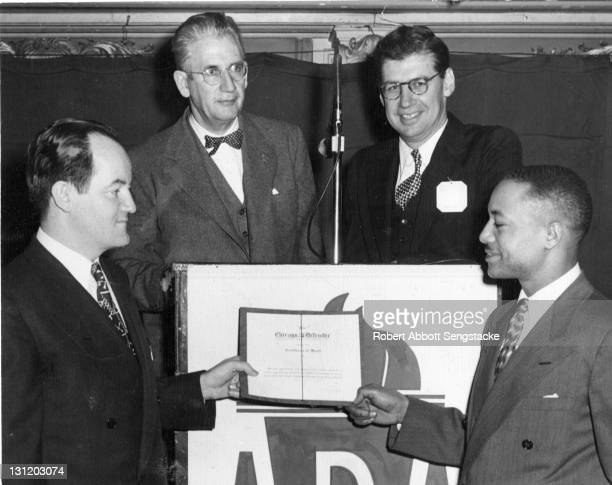 American newspaper publisher John H Sengstacke presents an award to politician Hubert Humphrey late 1940s or early 1950s