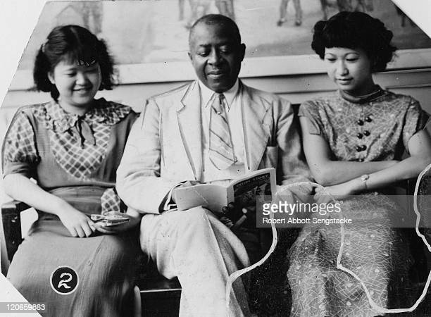 American newspaper publisher Robert Sengstacke Abbott reads with two unidentified Chinese students at Chicago Defender building, Chicago, Illinois,...