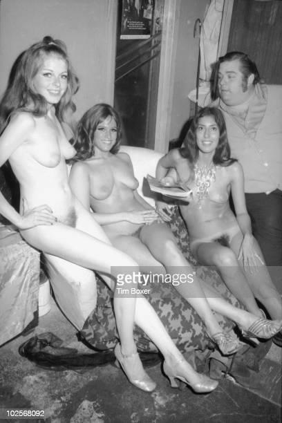 American nightclub promotor 'Big' Davey Rosenberg sits with three unidentigied burlesque dancers in the locker room backstage at the Condor Club one...