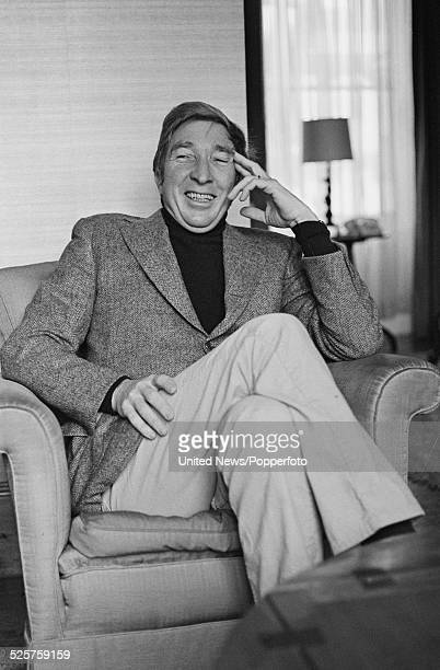 American novelist and critic John Updike pictured sitting in an armchair in London on 22nd March 1979