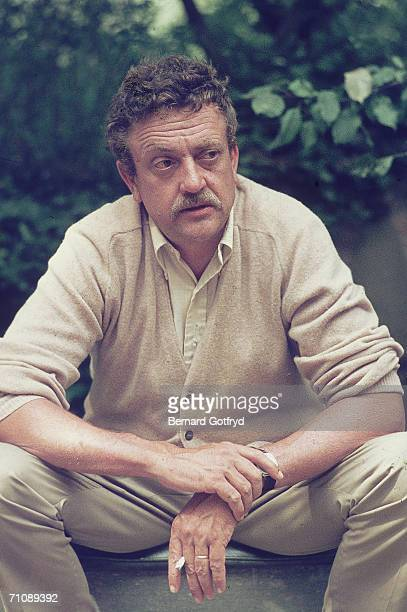American novelist and humanist Kurt Vonnegut wears a cardigan sweater as he sits on a step and smokes a cigarette, probably a Pall Mall, early 1970s.