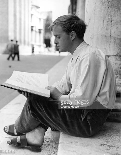 American novelist short story writer and playwright Truman Capote sits on the front steps of his house and reads a manuscript Venice Italy 1950s