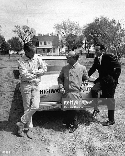 American novelist short story writer and playwright Truman Capote leans against the truck of a highway patrol police car and talks to an unidentified...