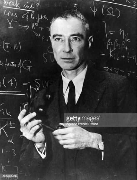 American nuclear physicist and father of the atom bomb Robert Oppenheimer stands in front of blackboard with scientific problems written on it 1940s...