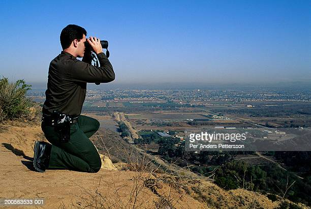 American officer of Border Patrol on hill observing Mexican border