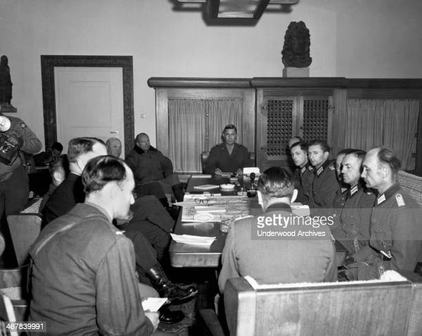 American officers on the left side of the table and German officers on the right side discuss the unconditional surrender of German Army Group G Haar...