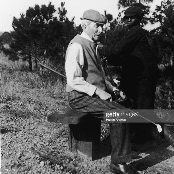 American oil businessman John D Rockefeller sits on a bench next to his caddy holding a golf club circa 1920