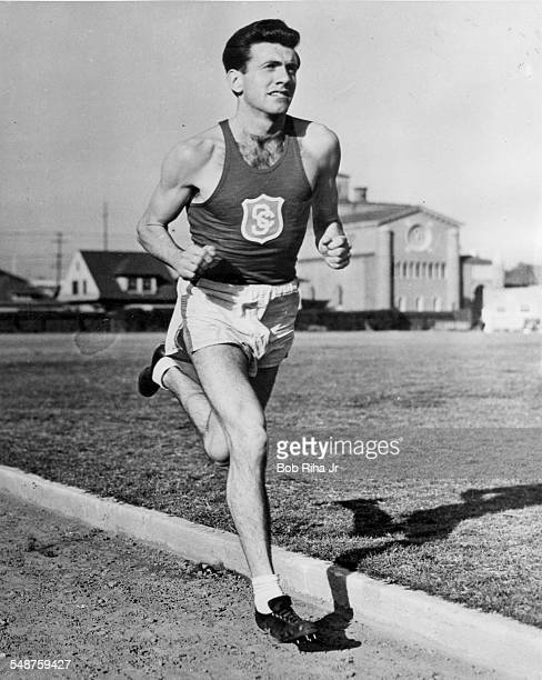 American Olympic athlete Louis Zamperini runs on a track for the University of Southern California, late 1930s.
