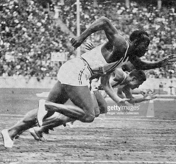 American Olympic runner Jesse Owens and his competitors leap forward from the starting line of the 100 meter dash Olympiastadion Berlin Germany...