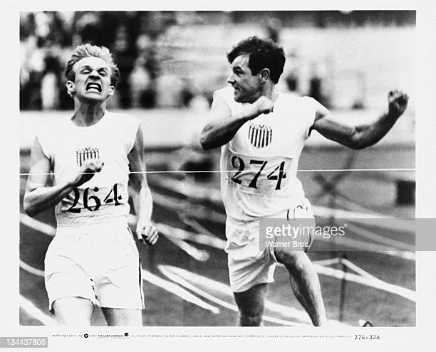 American Olympic runners Charlie Paddock and Jackson Scholz cross the finish line in the 200 Metres event at the 1924 Olympics in a scene from...