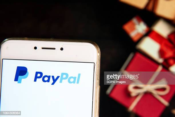 American online payment platform owned by Paypal logo is seen on an Android mobile device with a Christmas wrapped gifts in the background