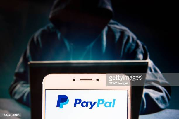 American online payment platform Paypal logo is seen on an Android mobile device with a figure of hacker in the background
