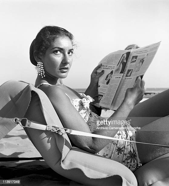 American opera singer Maria 'Callas' Kalogheropoulos liyng on a air mattress on Venice Lido beach wearing a floral swimsuit and dangling earrings...
