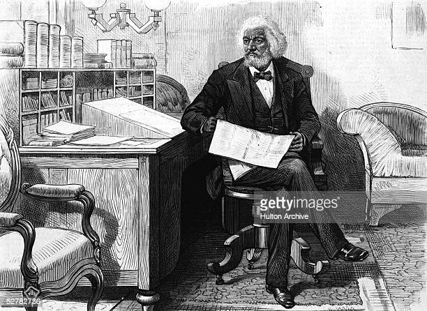 American orator editor author abolitionist and former slave Frederick Douglass edits a journal at his desk late 1870s
