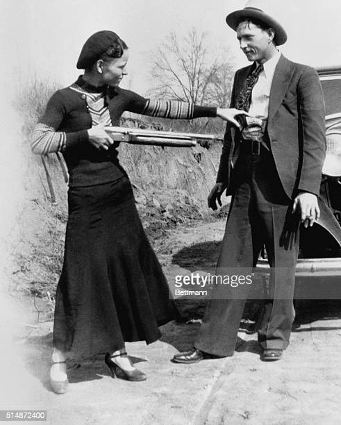 American outlaw Bonnie Parker, playfully points a shotgun at her partner Clyde Barrow in 1932. The two were well-known wanted criminals during a two...