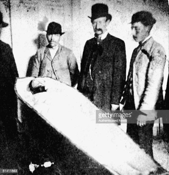 American outlaw Frank James and others pose over the dead ...