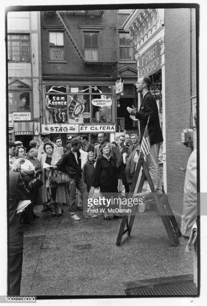 American pacifist activist and War Resisters League founder David McReynolds on a stepladder speaks to a crowd gathered on the sidewalk outside the...