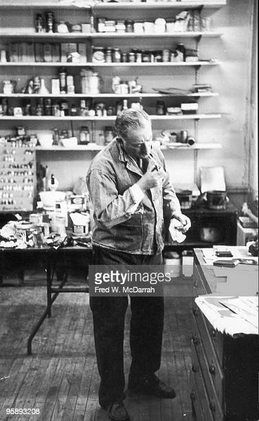 American painter Adolph Gottlieb lights a cigarette in his Chelsea studio New York New York February 16 1962