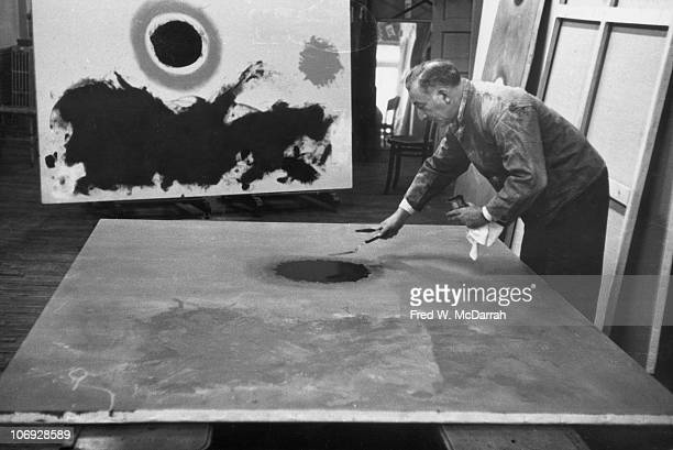 American painter Adolph Gottlieb works on a painting in his Chelsea studio New York New York February 16 1962
