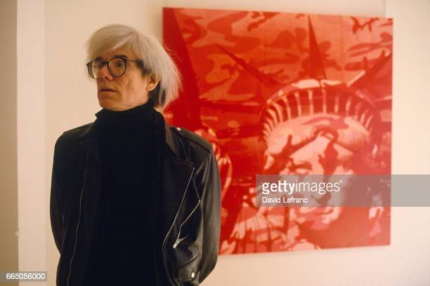 American Painter Andy Warhol, standing in front of a painting, circa 1970.