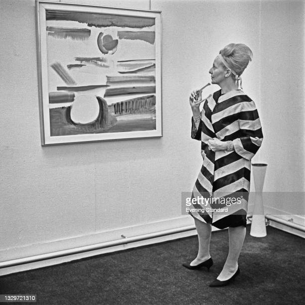 American painter Ann Cole-Phillips admires an artwork, UK, 21st May 1965.