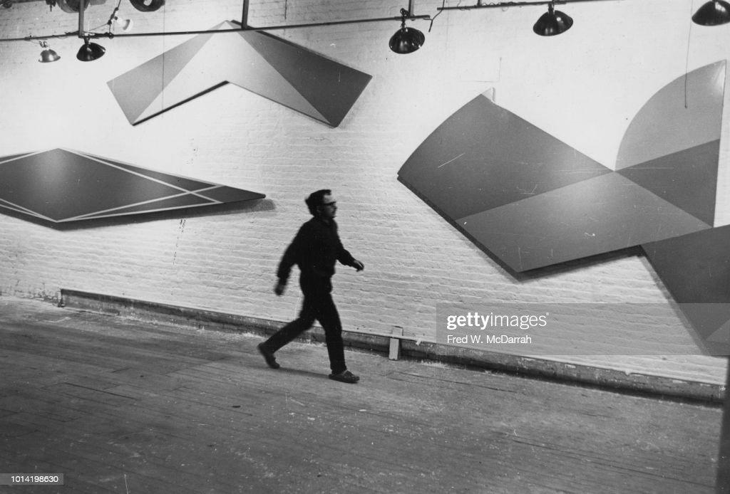 American painter Edwin Ruda walks past a wall of his work in his loft studio, New York, New York, November 12, 1965.