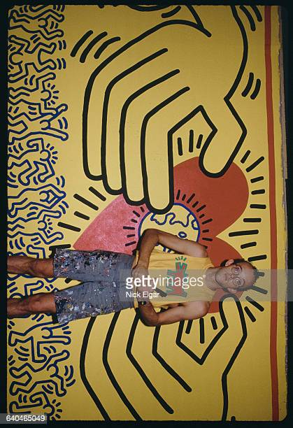 American painter Keith Haring takes a moment to pose with the mural he is currently working on