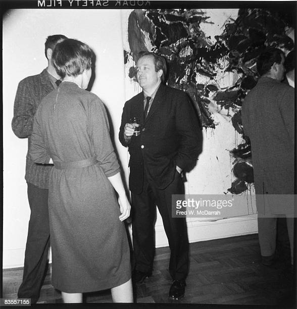 American painter Sam Francis speaks with an unidentified couple as they attend an event at the Martha Jackson Gallery New York New York February 25...