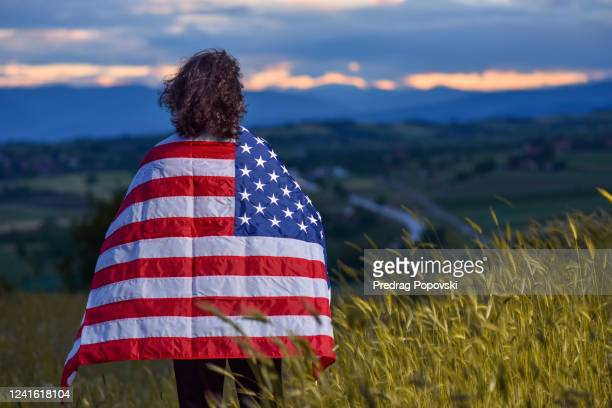 american patriot looking far away on horizon with usa flag wrapped around his neck - republican party stock pictures, royalty-free photos & images