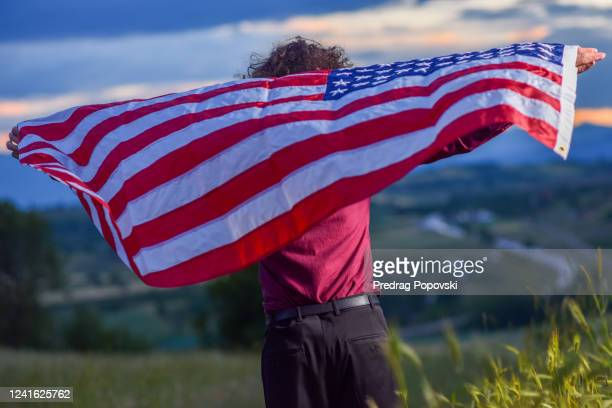 american patriot looking far away on horizon with usa flag wrapped around his neck - kumanovo stock pictures, royalty-free photos & images