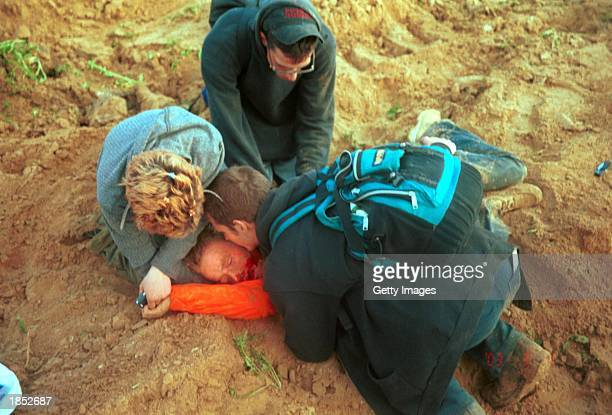 American peace activist Rachel Corrie lies bleeding while being helped by colleagues after she was run over by an Israeli bulldozer March 16 2003 in...