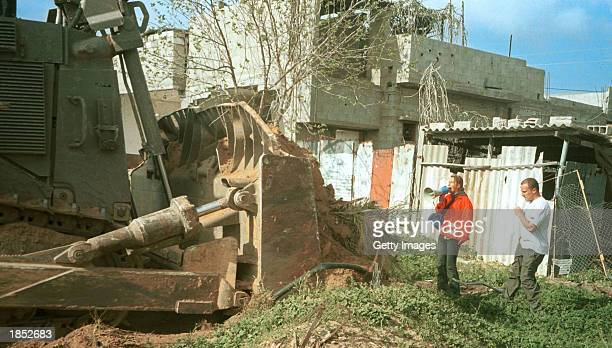 American peace activist Rachel Corrie stands between an Israeli buldozer and a Palestinian physician's house March 16 2003 in the Rafah refugee camp...