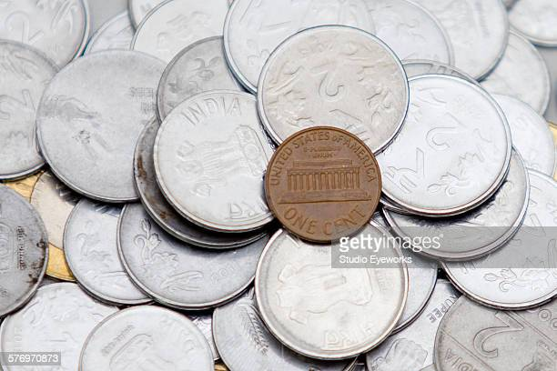 American penny over a heap of indian currency coin