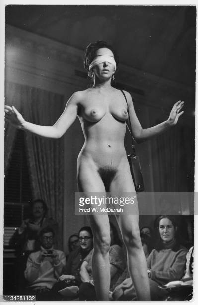 American performance and visual artist Carolee Schneemann naked but for a blindfolded and a handbag performs in a 'nude fashion show' performance New...
