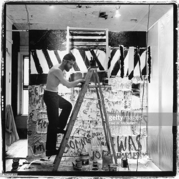 American performance artist Allan Kaprow climbs a ladder as he sets up an exhibition at the Ruben Gallery New York New York September 10 1959 The...