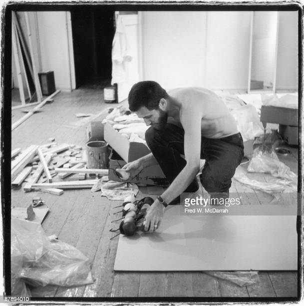 American performance artist Allan Kaprow glues wax fruit to a board as he sets up an exhibition at the Ruben Gallery New York New York August 27 1959...