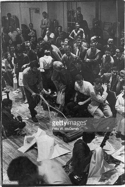 American performance artist Allan Kaprow uses a lawnmower to shred paper on the floor of Judson Hall before musicians and an audience at the Second...